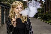 foto of exhale  - Pretty blond woman smoking an e - JPG