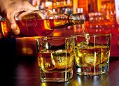 foto of whiskey  - barman pouring whiskey on bar table lounge bar atmosphere - JPG