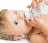 image of plastic bottle  - Pretty baby girl drinking milk from bottle - JPG