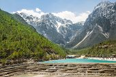 stock photo of jade blue  - White Water River waterfall and Jade Dragon Snow Mountain Lijiang Yunnan China - JPG
