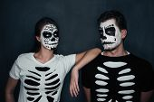 foto of gothic female  - Loving couple with skull face art in costume of skeletons on dark background Halloween theme