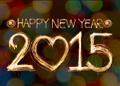stock photo of sparking  - Happy new year 2015 written with Sparkle firework on bokeh background - JPG