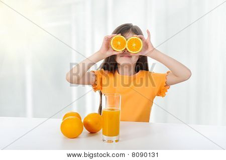 Girl At The Table With Oranges