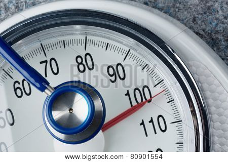 stethoscope and scale, symbolic photo for weight, diet and heart disease