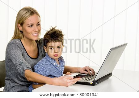 mother and son on the computer, symbol of home, family and career, double burden