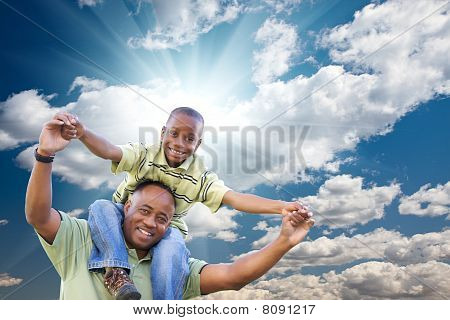 Happy African American Man With Child Over Clouds And Sky