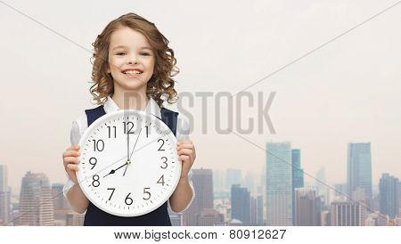 people, time management and children concept - smiling girl holding big clock showing 8 o'clock over city background