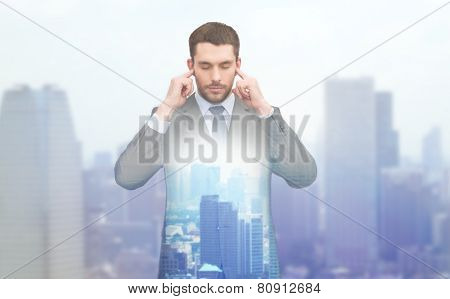 business, office and education concept - annoyed businessman covering his ears with his hands