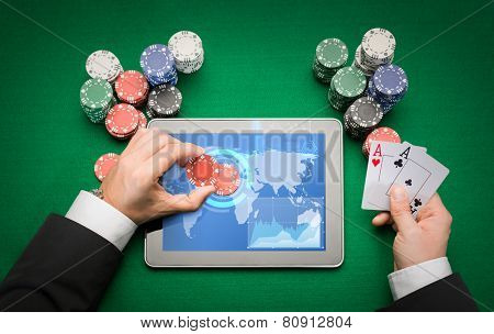 online casino, worldwide gambling, technology and people concept - close up of poker player with playing cards, tablet pc computer and chips at green casino table