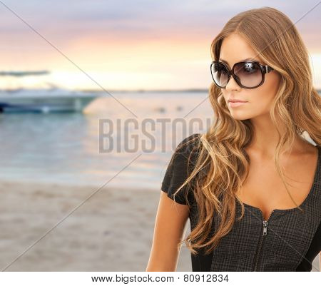 people, tourism and travel concept - beautiful young woman in shades over summer beach and boat background
