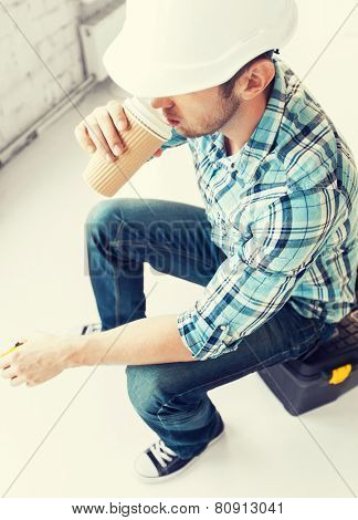 architect and home renovation concept - builder sitting on toolkit and drinking take away coffee