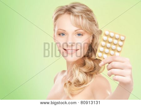 people, beauty, healthcare and medicine concept - happy young woman holding package of pills over green background