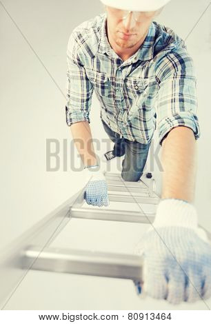 interior design and home renovation concept - man in helmet and gloves climbing ladder
