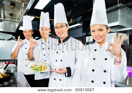 Asian Indonesian chefs along with other cooks in restaurant or hotel kitchen cooking or fry with a pan at the stove