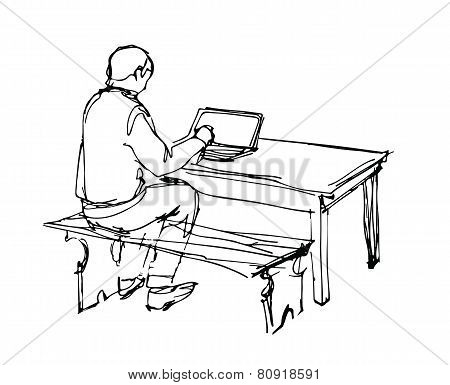 Man Working At A Laptop At The Table