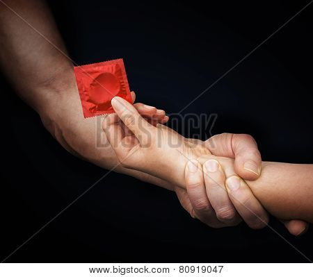 Man's Hand Holding Woman Hand With A Condom