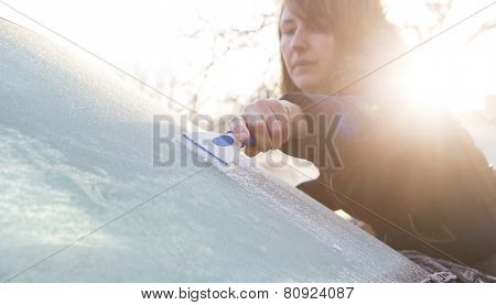 Woman Scraping Ice From Car Windshield
