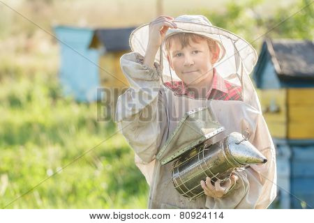 Teenage beekeeper using a smoker on bee yard