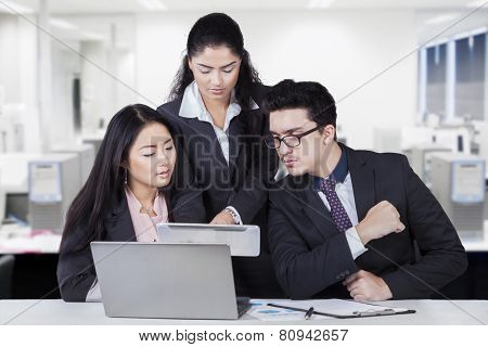 Businesswoman Showing Tablet At Her Partners