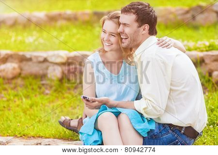 Portrait Of Two Caucasian Sweethearts Together Outdoors. Reading E-book And Smiling