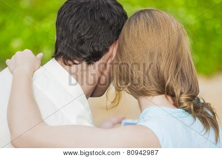 Back View Of Two Young Lovers Together Outdoors Reading E-book
