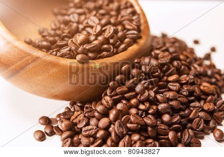 Closeup Of Woodden Bowl With Heap Of Arabica Coffee Beans On White Surface