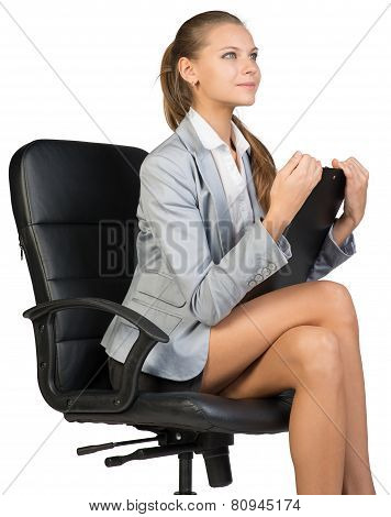Businesswoman sitting on office chair with clipbord in hands, looking ahead