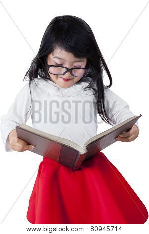 Little Schoolgirl Studying With A Textbook