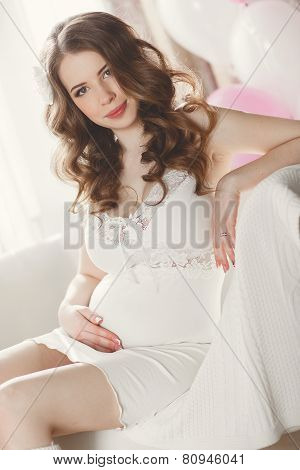 Pregnant woman in a white nightgown in the bedroom.