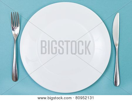Top View Of Porcelain Plate, Fork, Knife On Green
