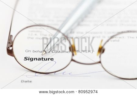Signature Of Contract And Pen Through Eyeglasses