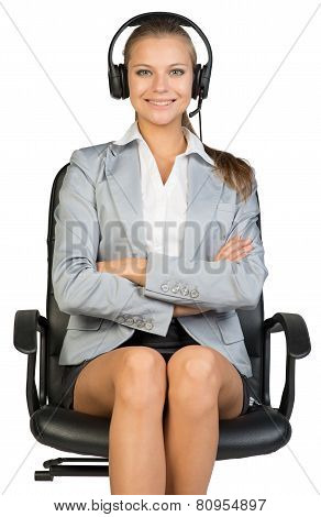 Businesswoman in headset sitting on office chair, smiling, her arms crossed