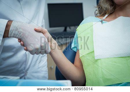 Close up mid section of male dentist shaking hands with woman