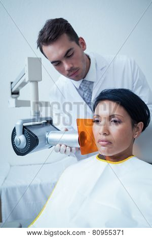 Serious young woman undergoing dental checkup in the dentists chair