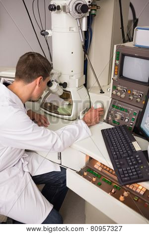 Biochemistry student using large microscope and computer at the university