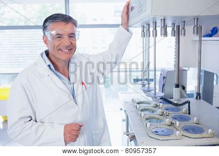 Smiling scientist with safety glasses in laboratory