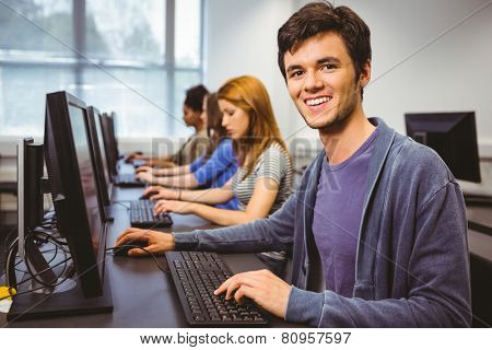 Happy student in computer class smiling at camera at the university
