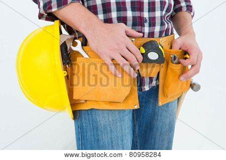 Close-up of male handyman with tool belt and handyman on white background
