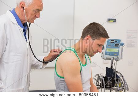 Doctor listening to patient with stethoscope at the medical centre
