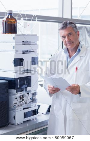 Scientist standing in lab coat holding a document in laboratory