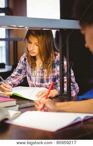 Serious student sitting at desk writing in notepad in library