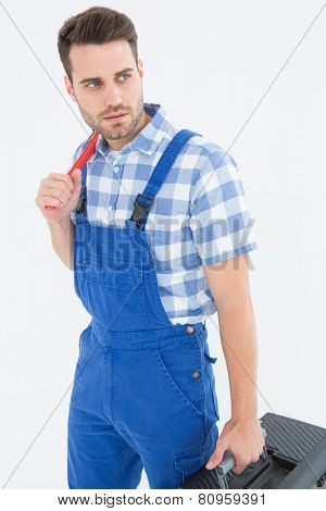 Confident young male repairman carrying toolbox while looking asway on white background