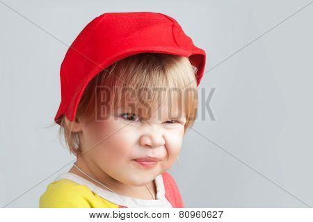 Portrait Of Funny Smiling Baby Girl In Red Baseball Cap