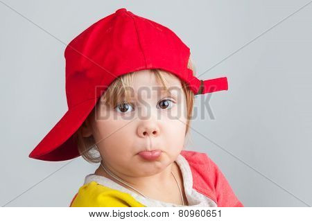 Portrait Of Funny Confused Baby Girl In Red Baseball Cap