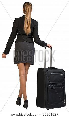 Businesswoman with wheeled travel bag makes step forward