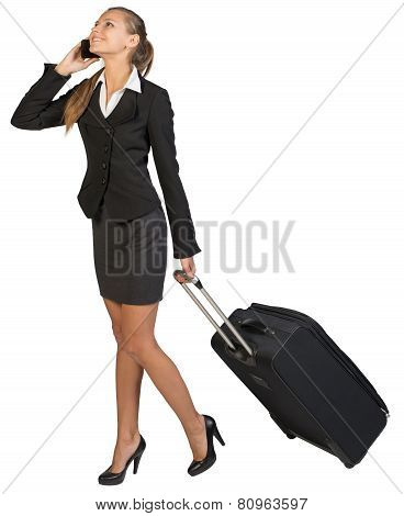 Businesswoman walking with wheeled suitcase, talking on the phone, smiling