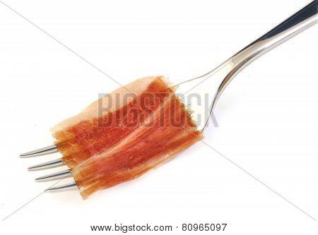 Spanish serrano ham slice on metal fork.