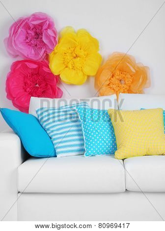 White sofa with colorful pillows in room on bright wall background