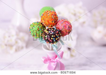 Sweet cake pops in vase on table on light background
