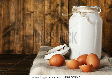 Milk can with eggs and eggshell on rustic wooden background